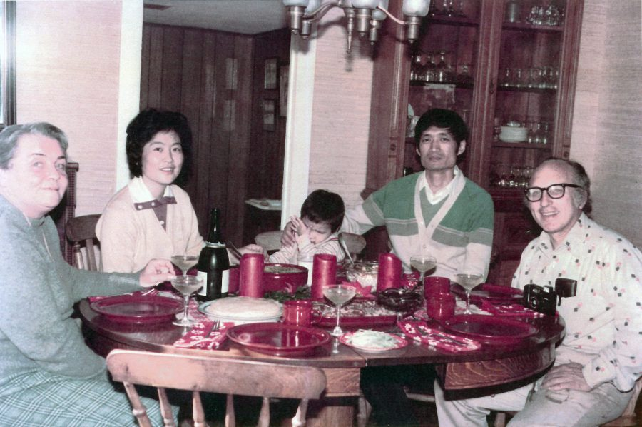 Qin Xu and his family sitting around a table with former NSSL Director Edwin Kessler's family on their farm in 1984 celebrating Christmas.