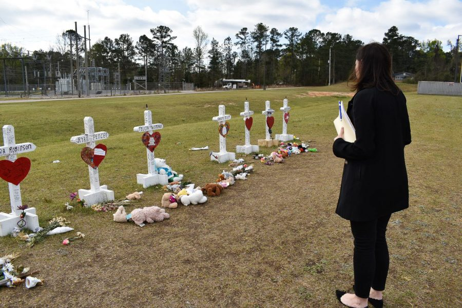 Kim Klockow-McClain stands at memorial crosses