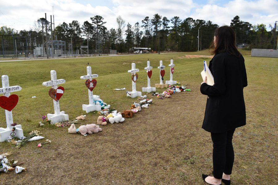 Kim Klockow-McClain stands at memorial crosses