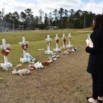 Woman views line of memorial crosses