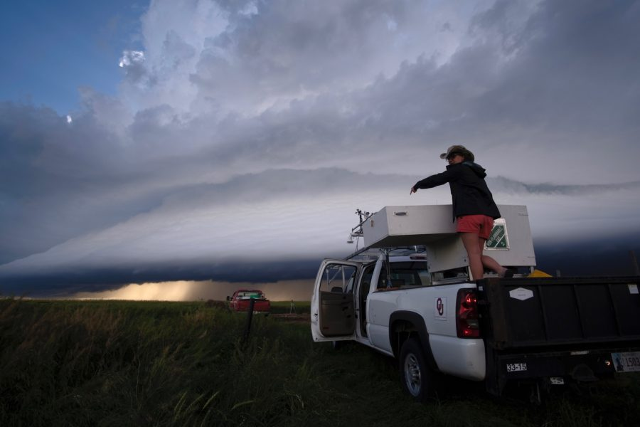 A researcher in a truck preparing equipment before a storm