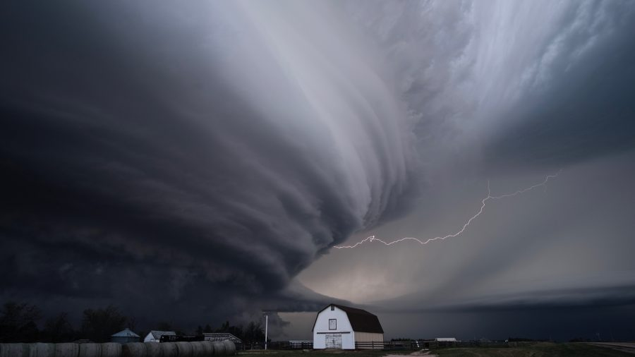 A supercell thunderstorm with lightning and a barn.