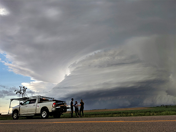 A photo of researchers launching a weather balloon in front of a storm.