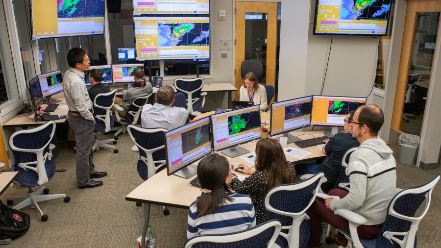 Researchers and forecasters testing new forecasting technologies on a computer screen.