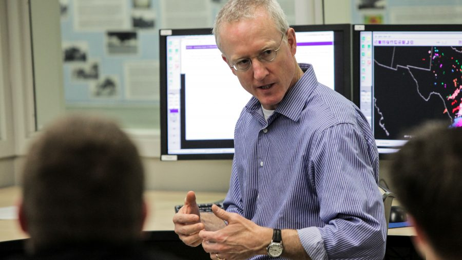 Jack Kain speaking to someone in the NOAA Hazardous Weather Testbed room