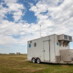 A mobile research trailer parked in a grassy field. The sky is cloudy and blue above.