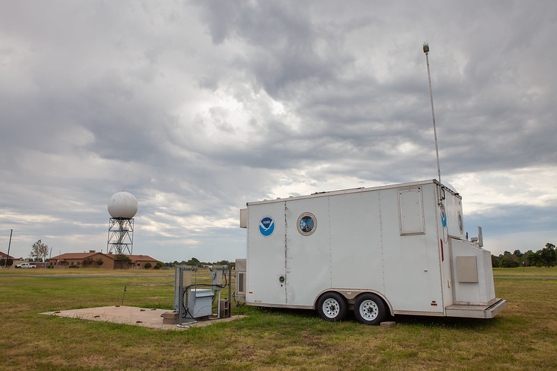 A research trailer known as CLAMPS parked in a grassy field near a power connector. In the background is an operational radar. The sky is overcast, cloudy and gray.