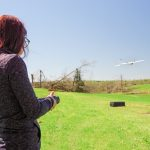 A woman hold a remote control, which flies a UAS in the distance.