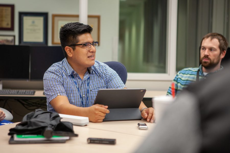 Joseph Trujillo sitting at a table with a computer tablet in front of him.