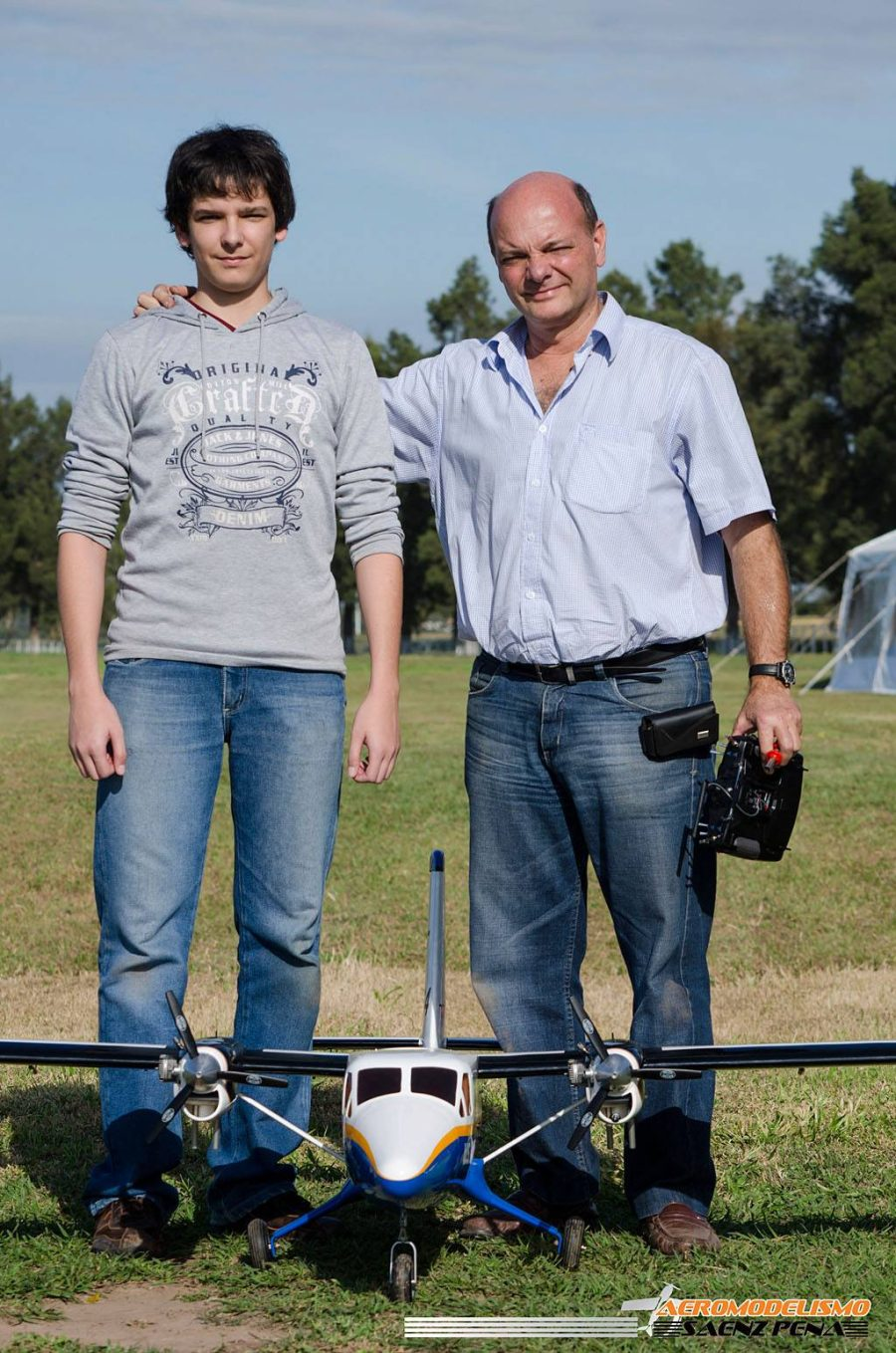 Two men standing in front of a small model plane aircraft